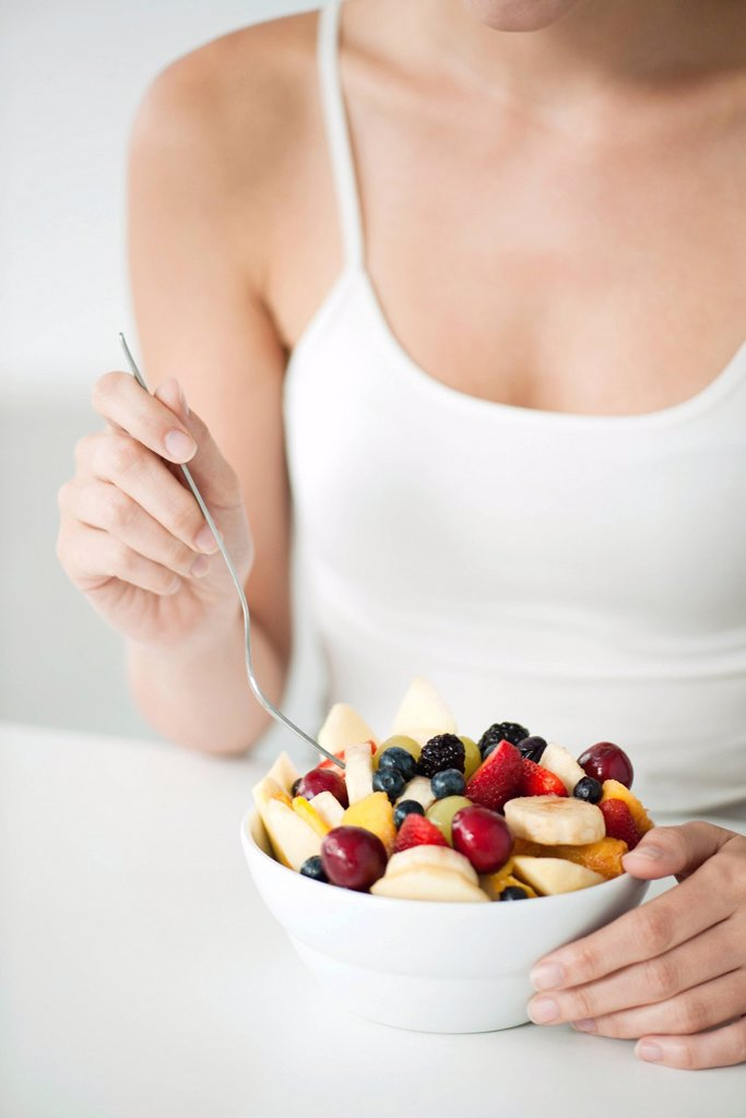 Stock Photo: 1569R-9075785 Woman with fruit bowl, mid section