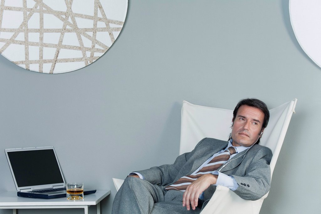 Mature businessman relaxing on chair with earphones : Stock Photo