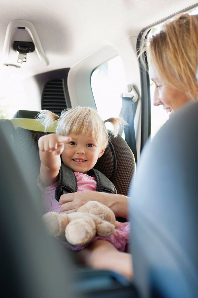 Stock Photo: 1569R-9075861 Little girl pointing and smiling as her mother fastens her into car seat