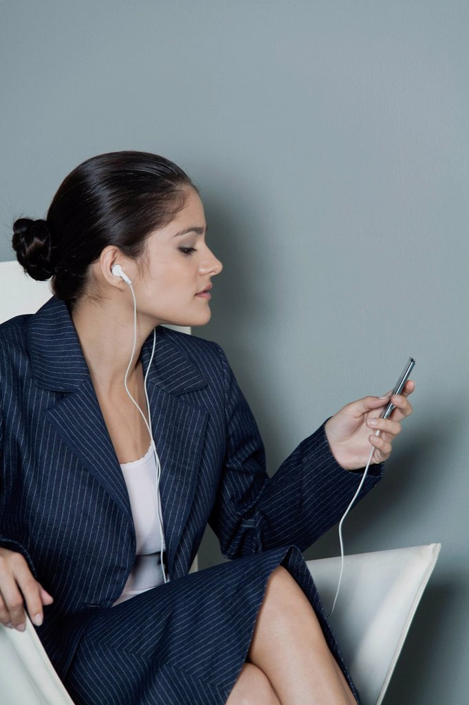 Stock Photo: 1569R-9075945 Young businesswoman listening to MP3 player