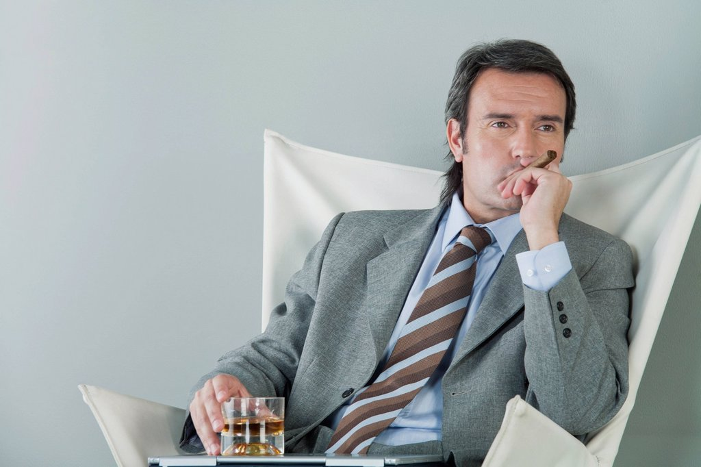Mature businessman relaxing with drink and cigar : Stock Photo