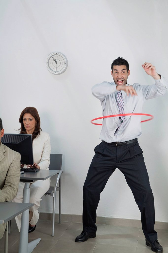 Young businessman playing with hula hoop in office while colleagues work : Stock Photo
