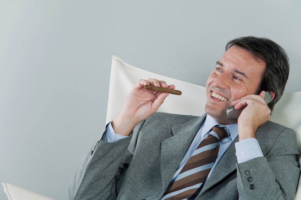 Mature businessman using cell phone and smoking cigar : Stock Photo
