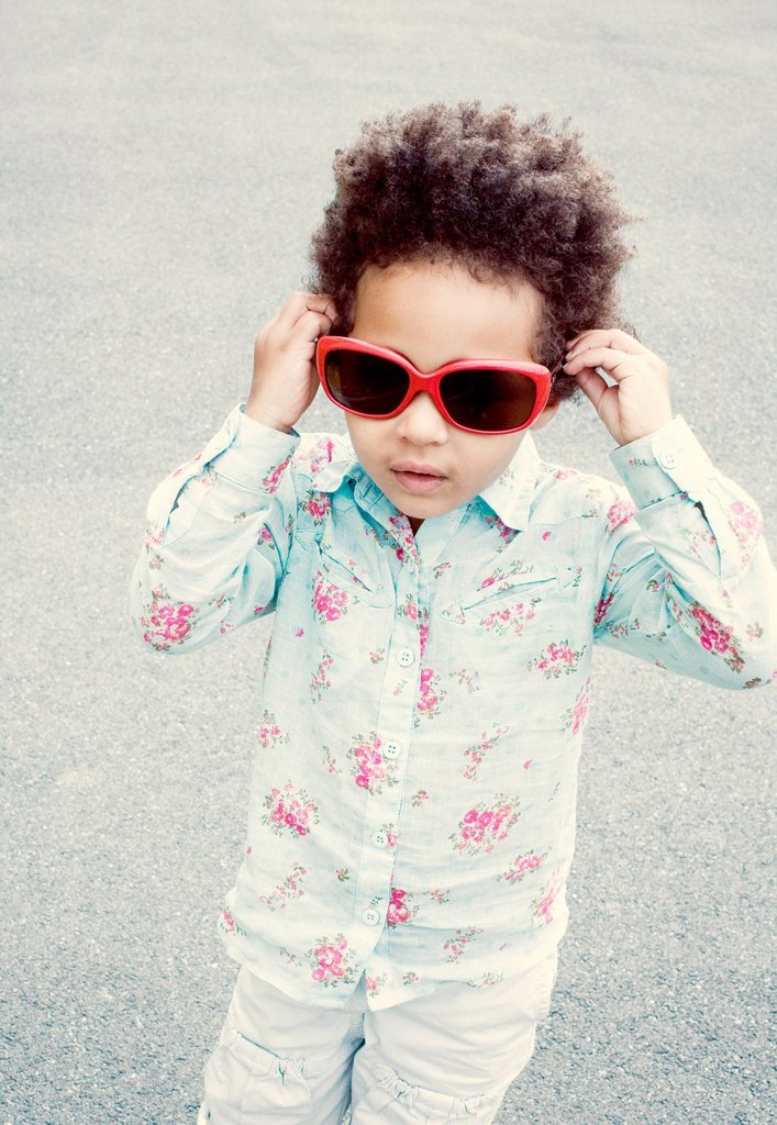 Stock Photo: 1569R-9076047 Little girl putting on sunglasses
