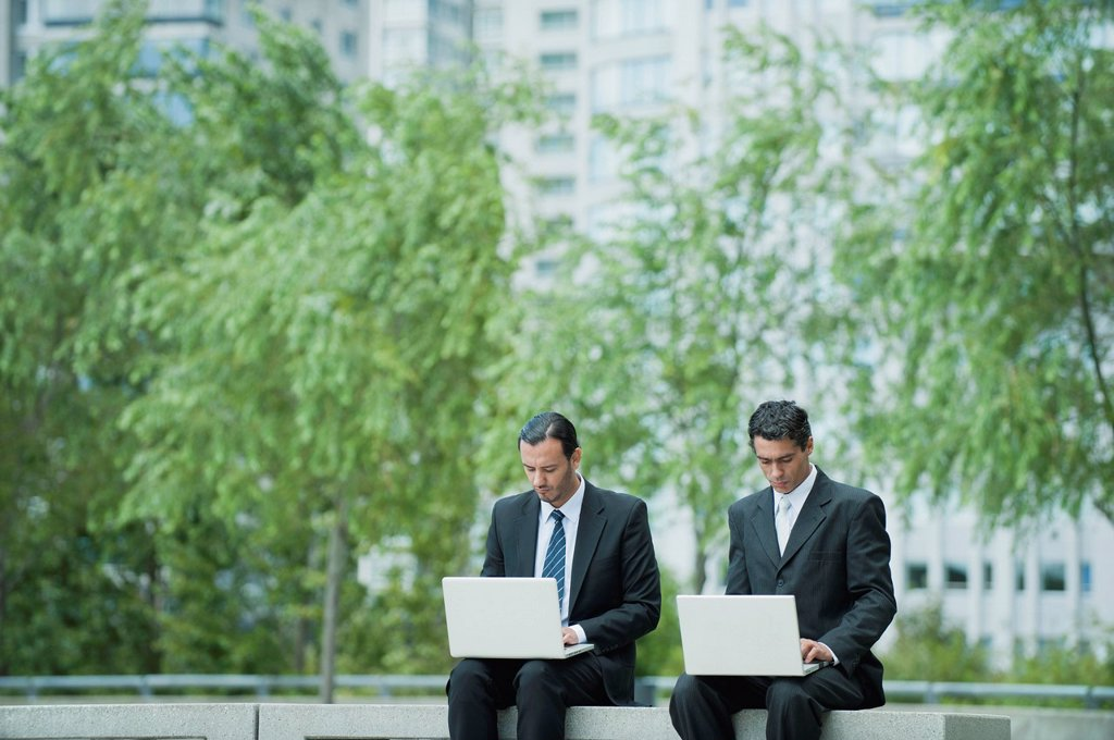 Stock Photo: 1569R-9076149 Businessmen sitting side by side using laptop computers outdoors