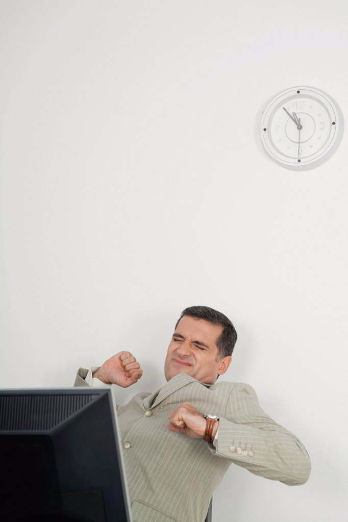 Mature businessman stretching at desk : Stock Photo