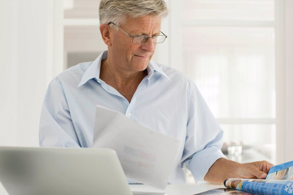 Senior man working on laptop computer at home : Stock Photo