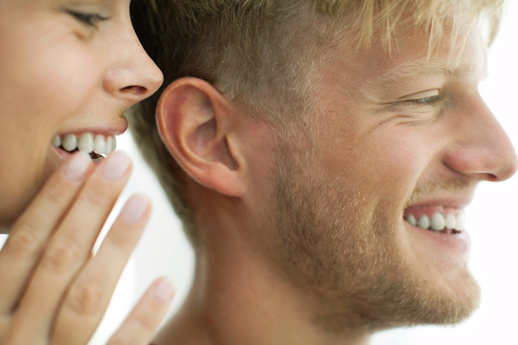 Stock Photo: 1569R-9076347 Woman whispering in man´s ear, close_up