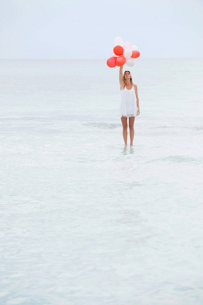 Stock Photo: 1569R-9076404 Woman standing on surface of water, holding bunch of balloons