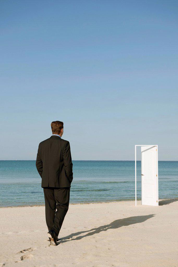 Stock Photo: 1569R-9076524 Businessman walking on beach towards half_open door, rear view