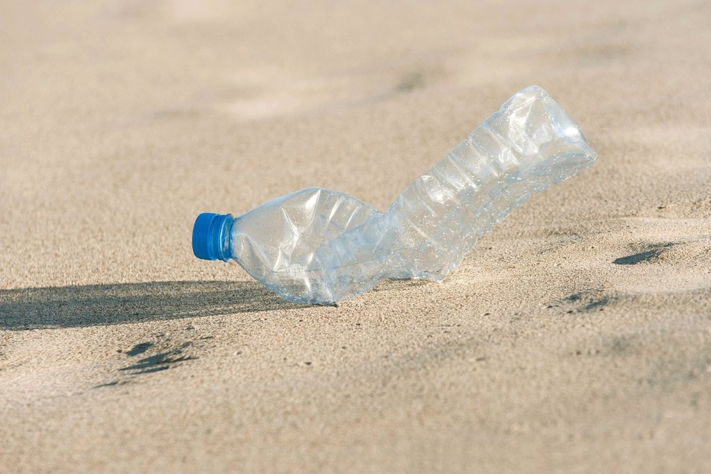 Stock Photo: 1569R-9076529 Empty plastic bottle on beach, close_up
