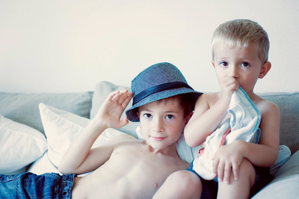 Stock Photo: 1569R-9076571 Young brothers together on sofa, portrait