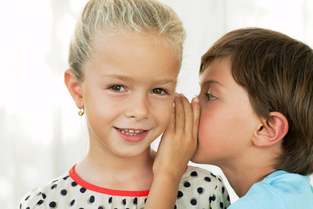 Boy whispering in girl´s ear : Stock Photo