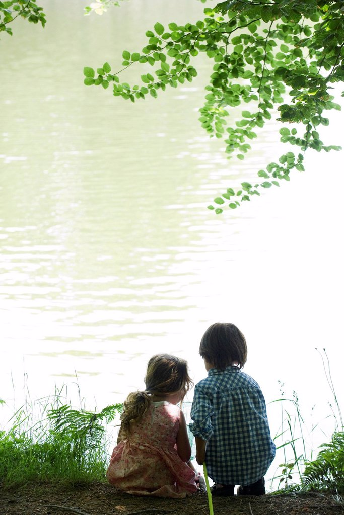 Stock Photo: 1569R-9076753 Children by lake with fish net, rear view, backlit