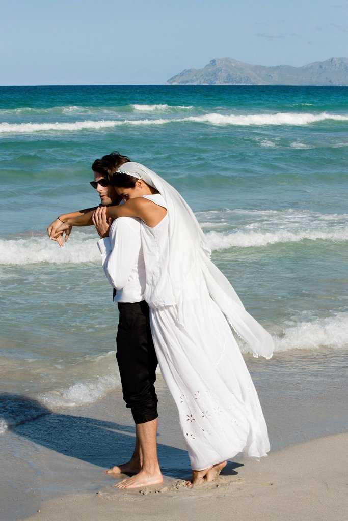 Bride and groom embracing at the beach : Stock Photo