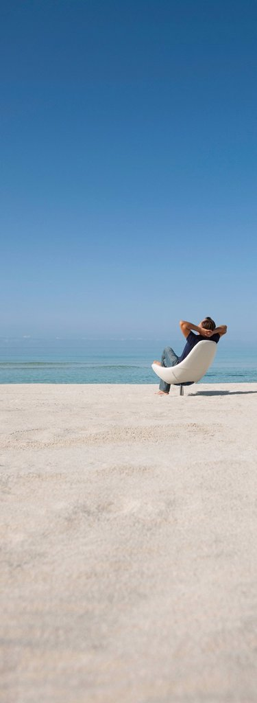 Stock Photo: 1569R-9076810 Man relaxing in chair on beach, rear view