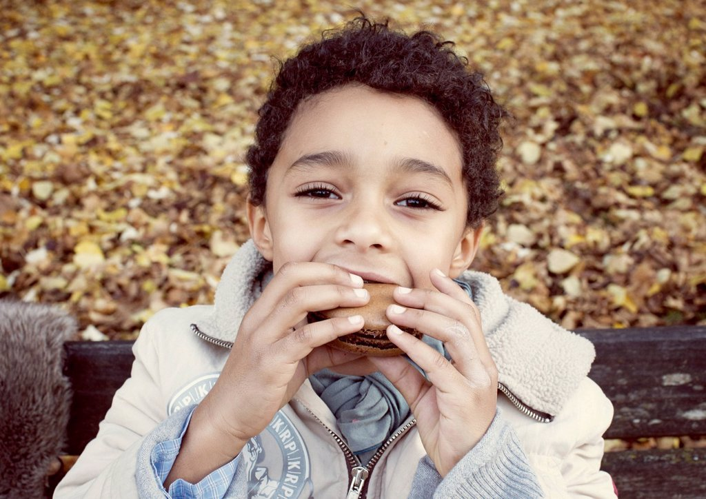 Stock Photo: 1569R-9076838 Boy eating macaroon, portrait