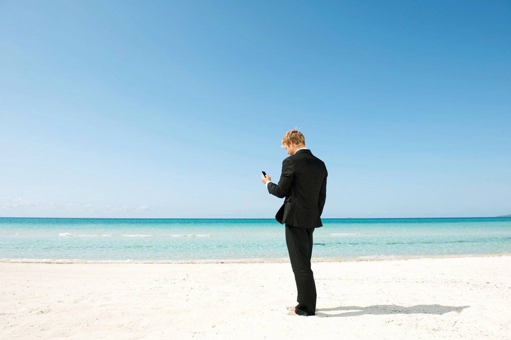 Stock Photo: 1569R-9076973 Businessman using cell phone on beach