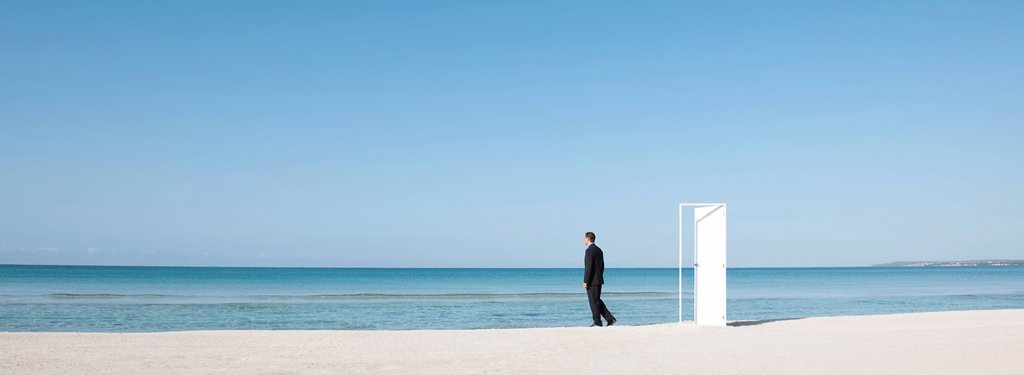 Businessman standing on beach next to half_open door, looking at ocean : Stock Photo
