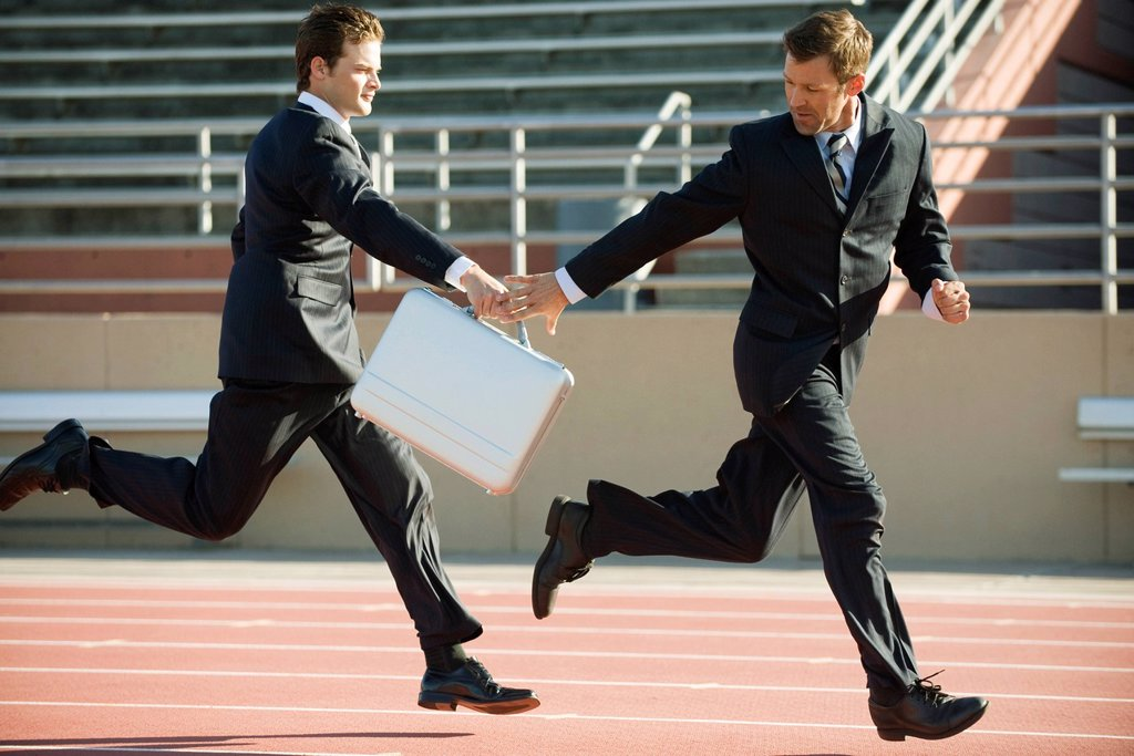 Stock Photo: 1569R-9077146 Businessmen handing off briefcase in relay race