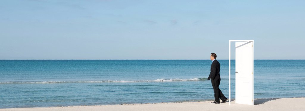 Stock Photo: 1569R-9077307 Businessman standing on beach next to half_open door, looking at ocean