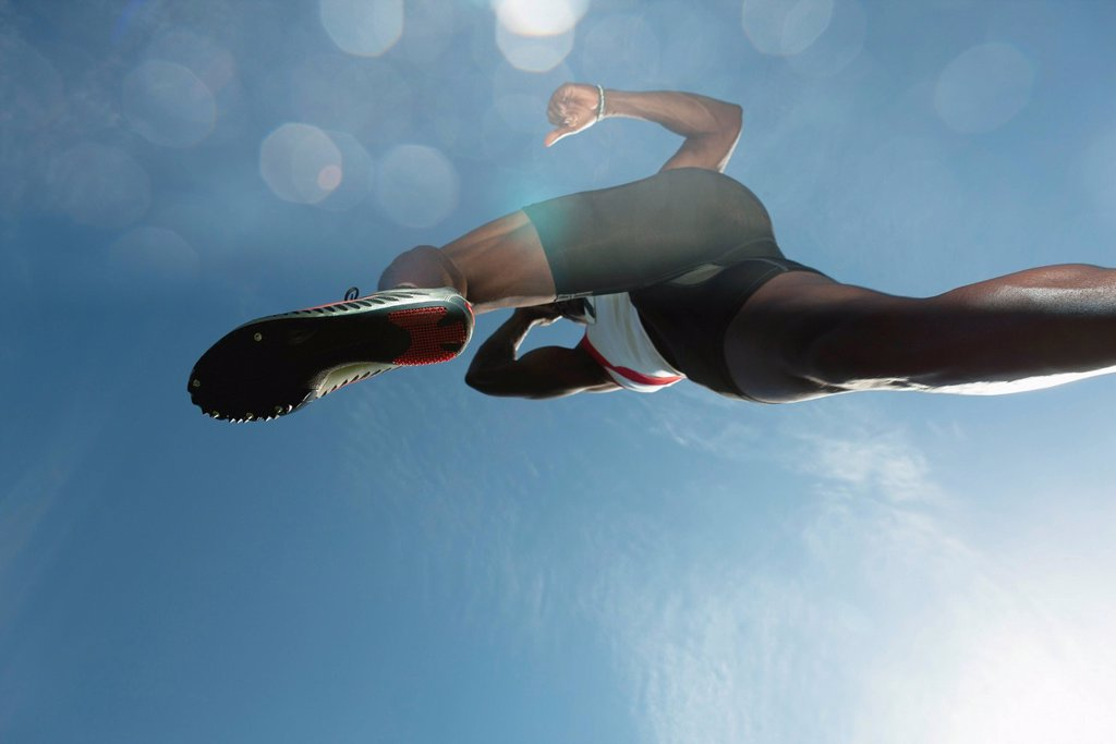 Athlete in midair, low angle view : Stock Photo
