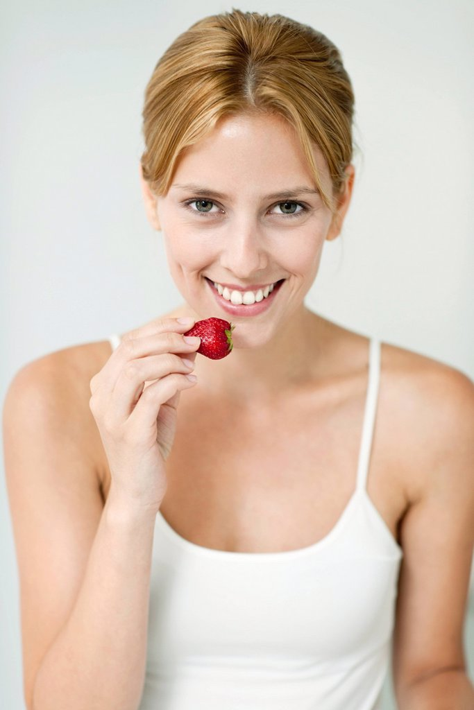 Stock Photo: 1569R-9077493 Young woman eating strawberry, portrait