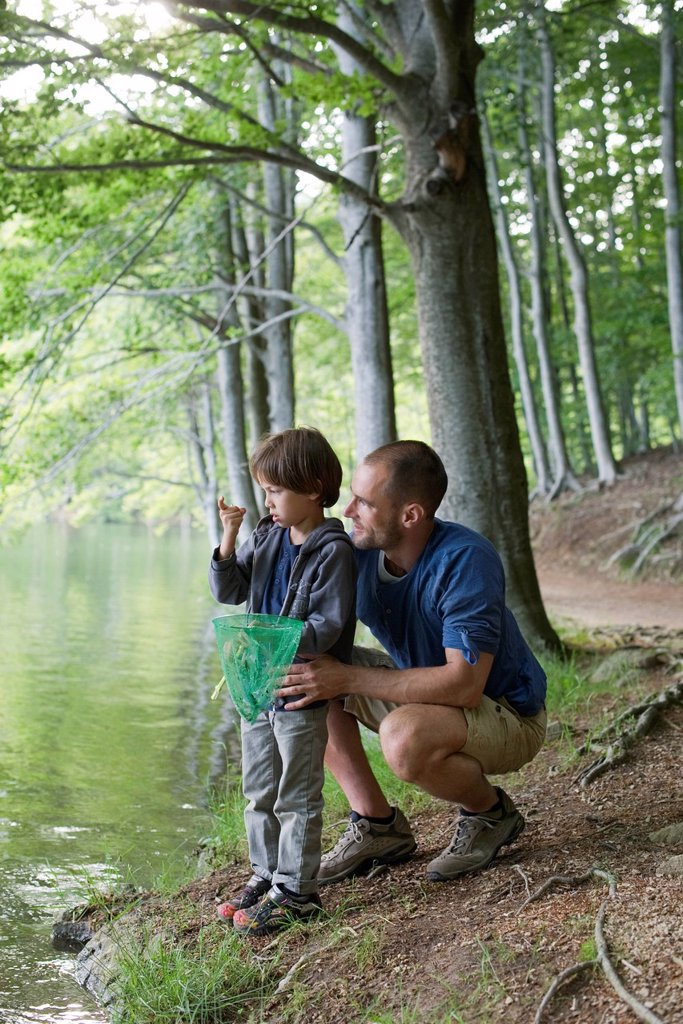 Stock Photo: 1569R-9077519 Father and son fishing, boy staring at tiny fish in hand