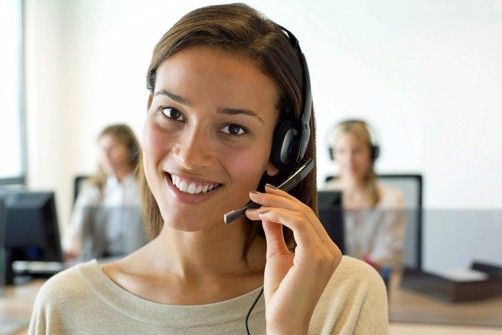 Woman using headset in office, portrait : Stock Photo