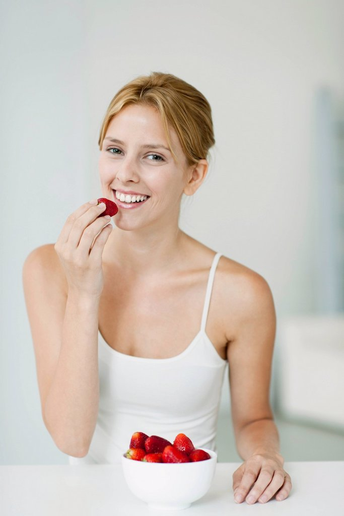 Young woman with bowl of strawberries, portrait : Stock Photo