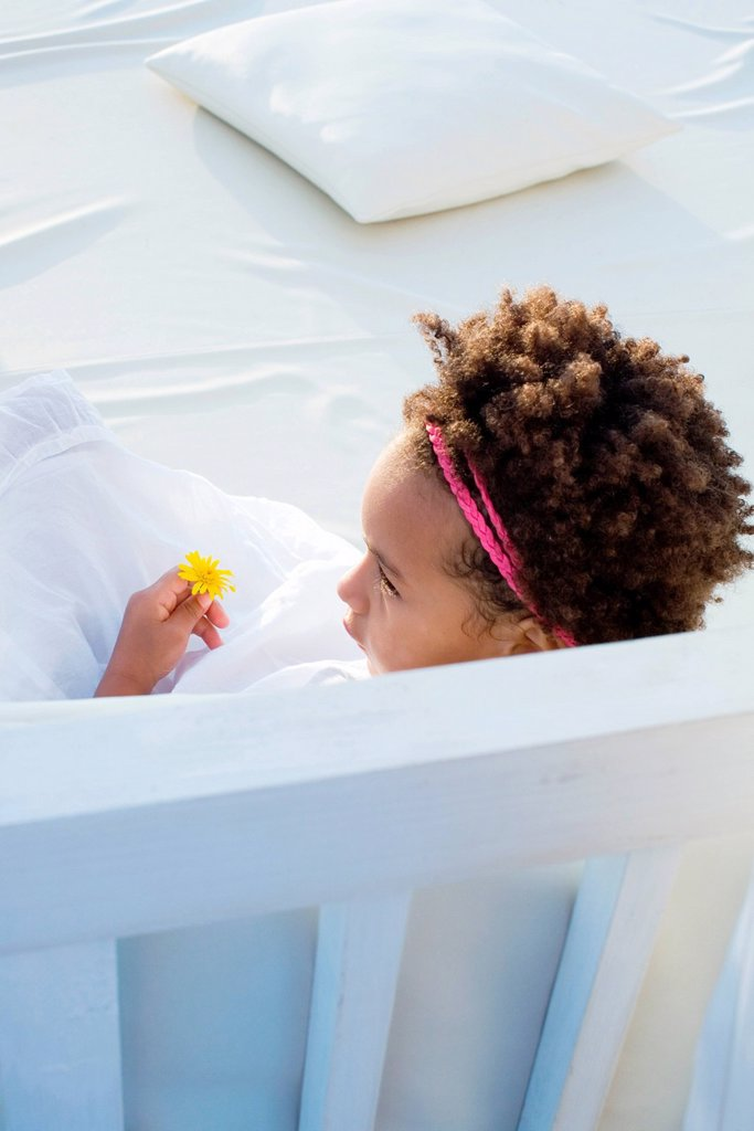 Stock Photo: 1569R-9077633 Little girl relaxing with flower in hand