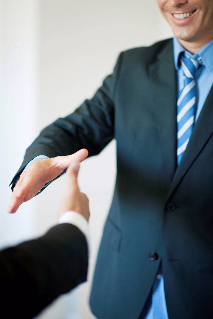 Executives extending hands to shake, cropped : Stock Photo