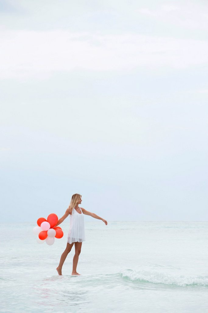 Woman walking on water, carrying bunch of balloons : Stock Photo