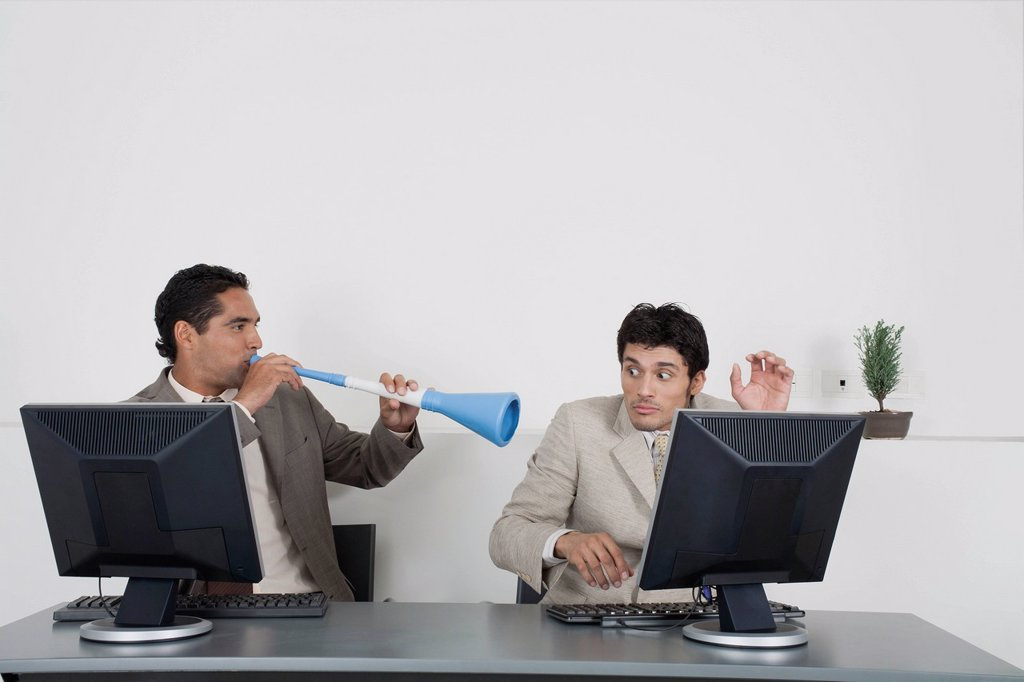 Businessman blowing vuvuzela horn into colleague´s ear : Stock Photo