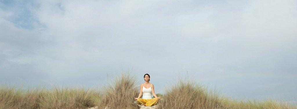 Mature woman meditating on beach : Stock Photo