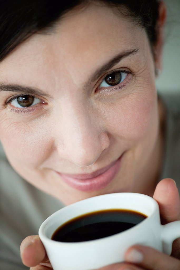 Mid_adult woman holding cup of coffee : Stock Photo