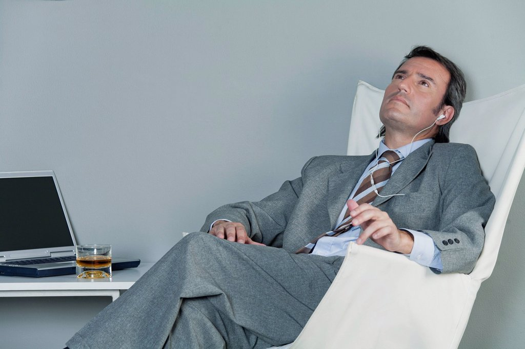 Stock Photo: 1569R-9078146 Mature businessman relaxing on chair with earphones