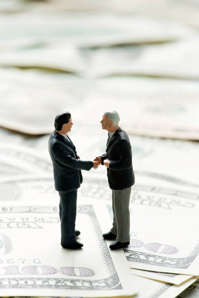 Stock Photo: 1569R-9078290 Male figurines shaking hands on pile of one hundred dollar bills