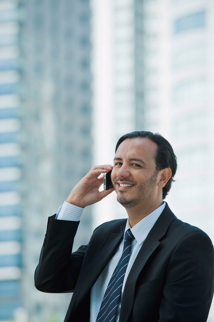 Stock Photo: 1569R-9078292 Business executive using cell phone outdoors