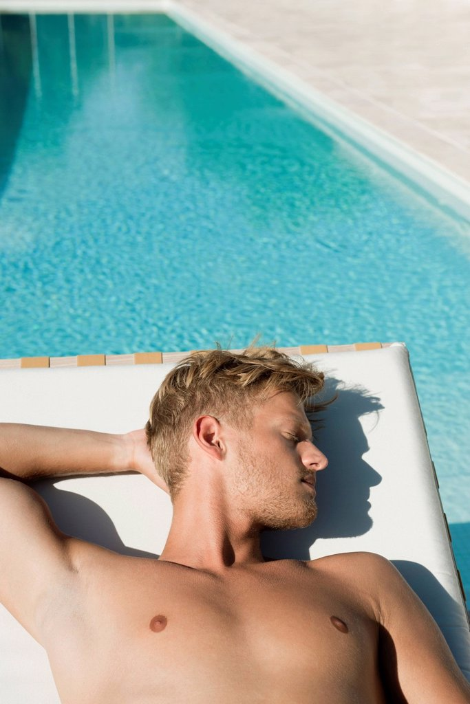 Stock Photo: 1569R-9078688 Man sunbathing beside pool