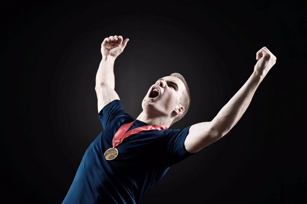 Male athlete shouting with arms raised in victory : Stock Photo