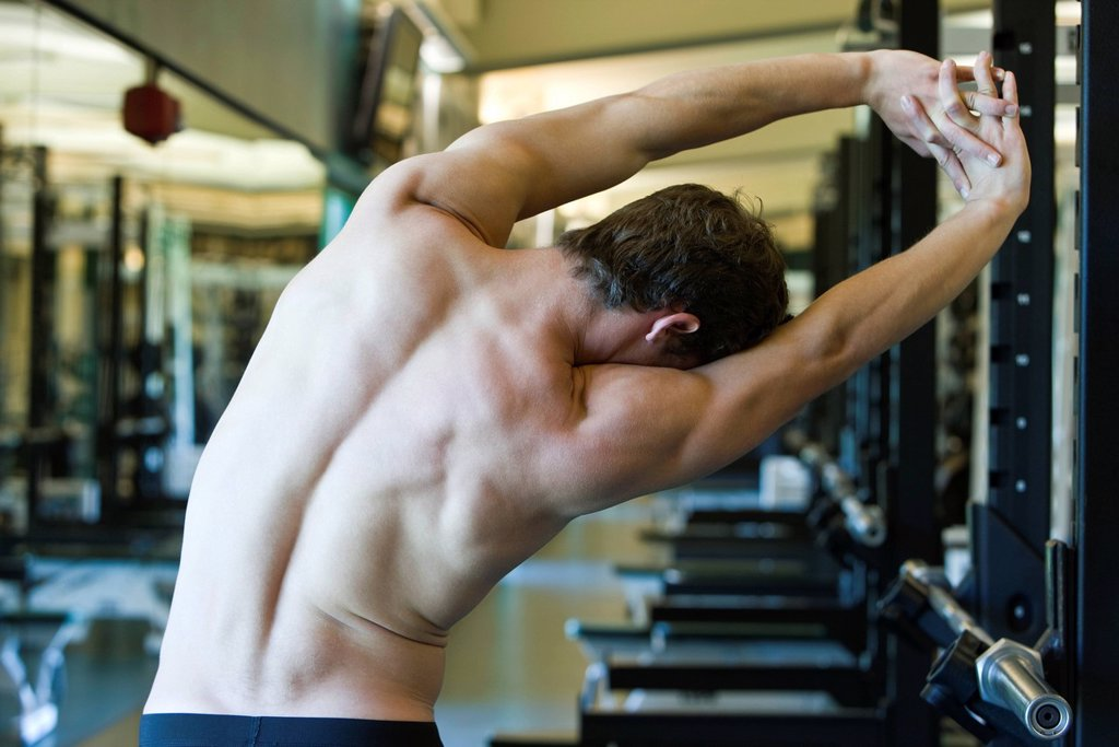 Stock Photo: 1569R-9078715 Barechested man stretching in weight room, rear view