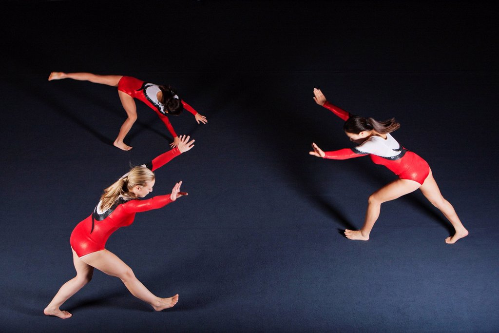 Stock Photo: 1569R-9078727 Female gymnasts practicing floor routine