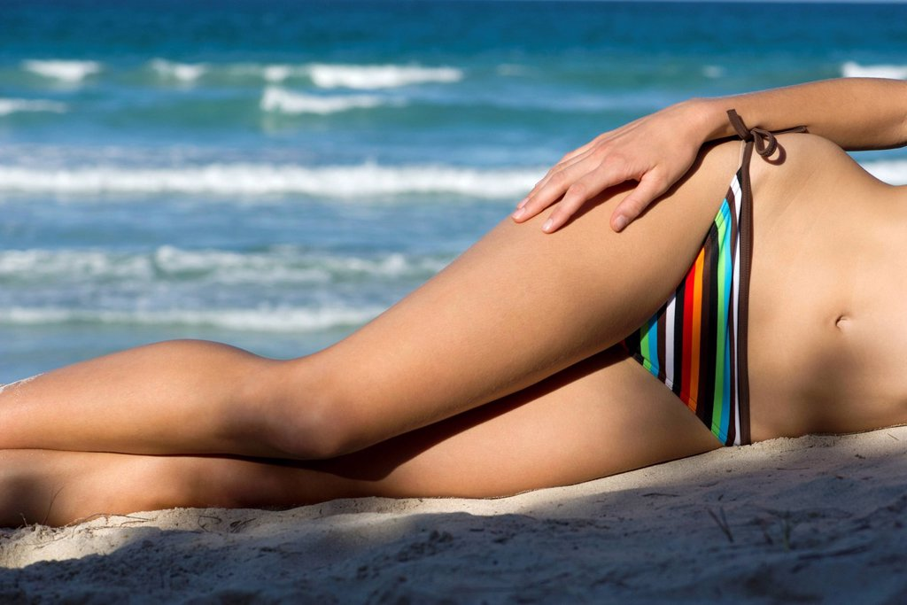 Stock Photo: 1569R-9078880 Woman in bikini lying on beach, low section