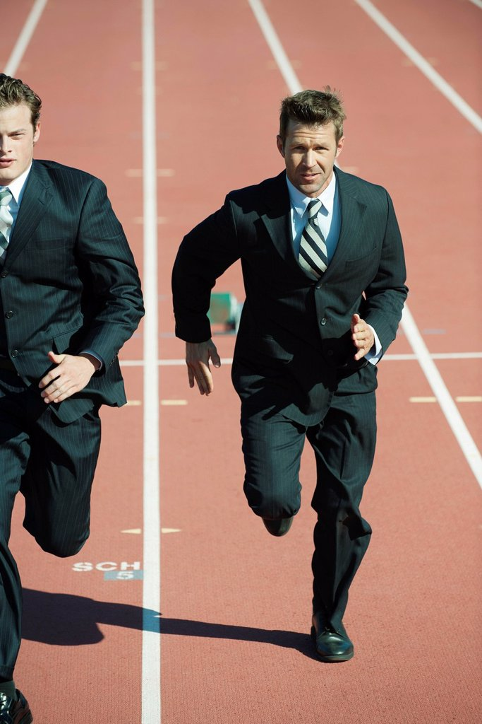 Stock Photo: 1569R-9078906 Businessmen racing each other on running track