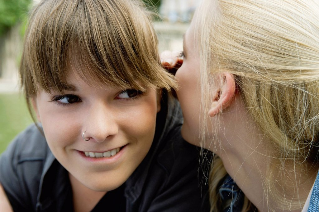 Stock Photo: 1569R-9078954 Young woman whispering in her friend´s ear