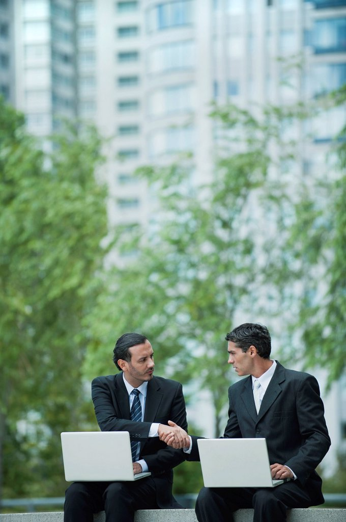 Stock Photo: 1569R-9078985 Business executives sitting outdoors with laptop computers, shaking hands