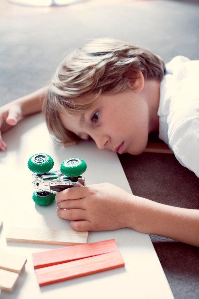 Stock Photo: 1569R-9079065 Boy playing with toy car