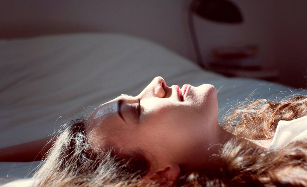 Stock Photo: 1569R-9079066 Mid_adult woman lying on bed, enjoying sunlight with eyes closed