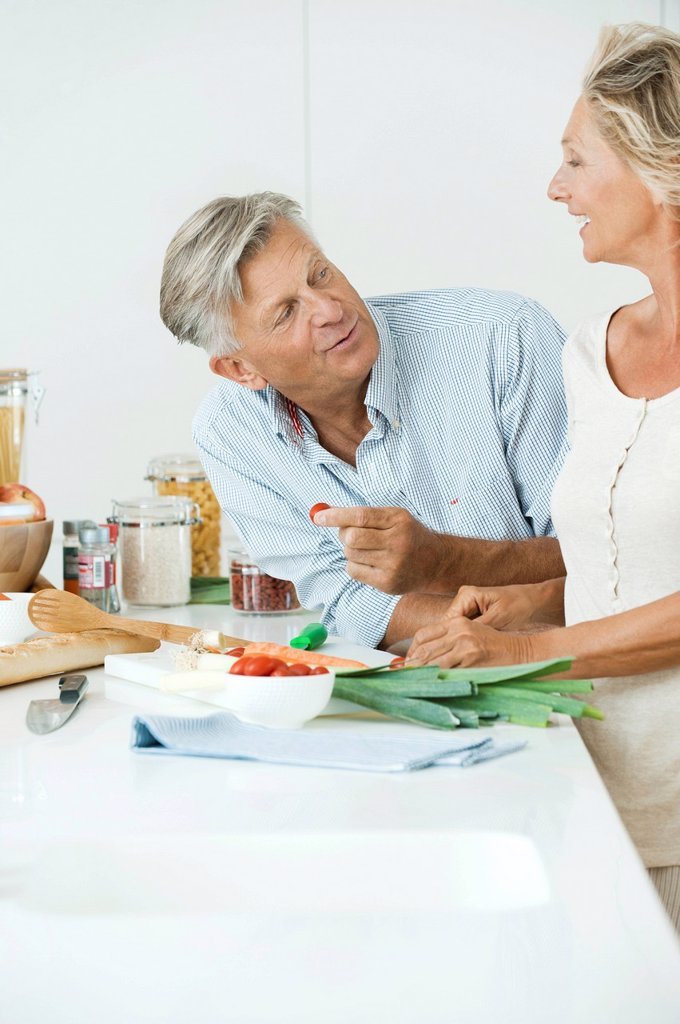 Mature couple preparing food together in kitchen : Stock Photo